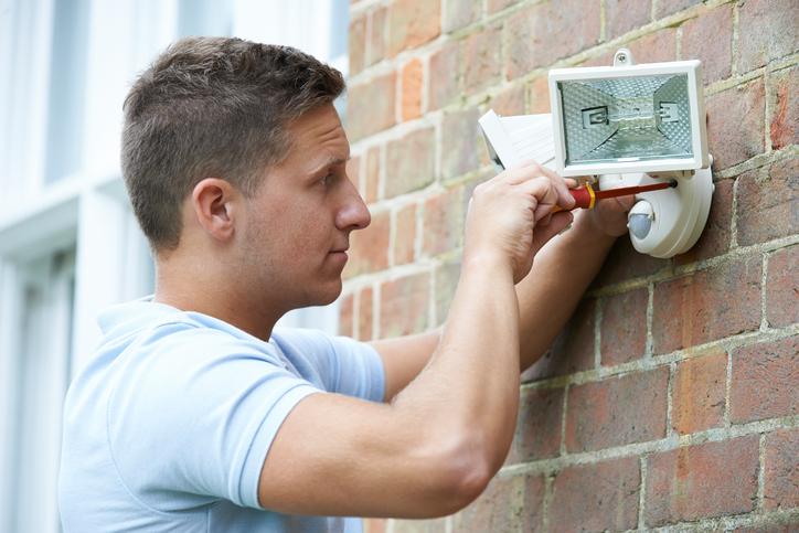 A man adjusting security lights on a home
