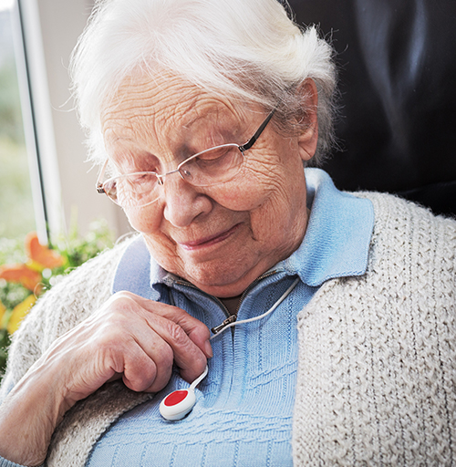 Elderly woman looking at her medical alert device